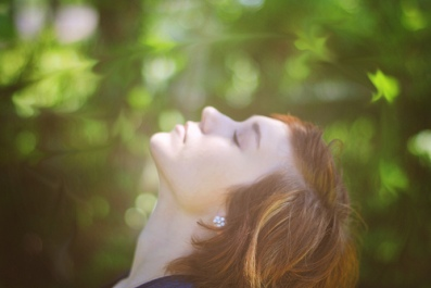 image of girl relaxing her head back and breathing in nature